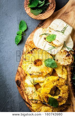 Grilled pineapple slices and fresh cheese with fresh mint on olive wooden cutting board, gray slate background. top view