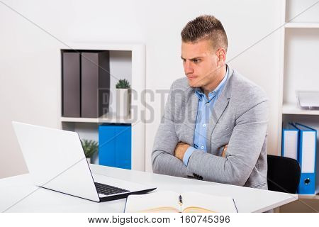 Angry businessman is sitting at his office and looking at his laptop.