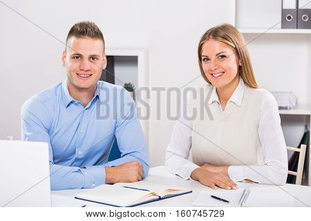 Businesswoman and businessman sitting in office and working together.
