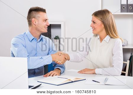 Businesswoman and businessman sitting in office and shaking hands.