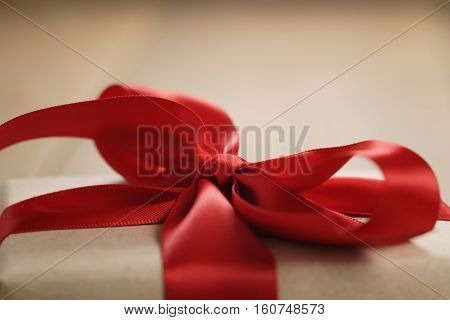 handmade gift brown paper box with red ribbon bow on wood table, close up shot