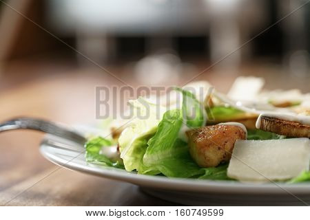 closeup shot of caesar salad with chicken on old wooden table, shallow focus