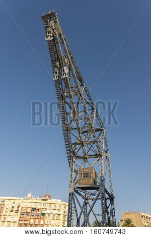 Old port cargo crane Valencia harbor over blue sky background