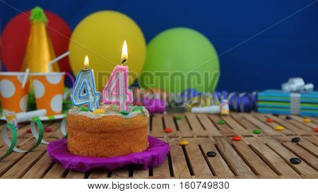 Birthday cake with candles on rustic wooden table with background of colorful balloons, gifts, plastic cups and candies with blue wall in the background. Focus is on cake