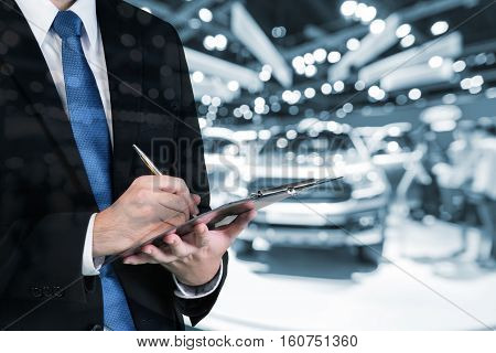 Double exposure of saleman hands holding trade booking with blurred background of new car displayed in showroom dealer buying new car.