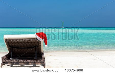 Sunbed with Christmas hat on a tropical beach