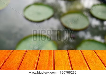 Empty top wooden table orange and lotus leaf blurred background Can use for product display.