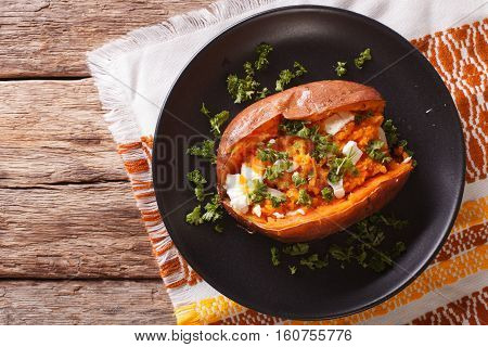 Whole Sweet Potato Baked With Cheese, Spices And Parsley Close-up On A Plate. Horizontal Top View