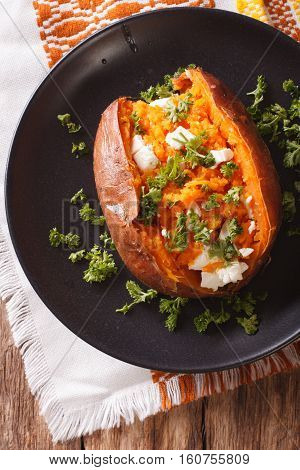 Orange Sweet Potatoes Baked With Cream Cheese, Spices And Herb Close-up On A Black Plate. Vertical T