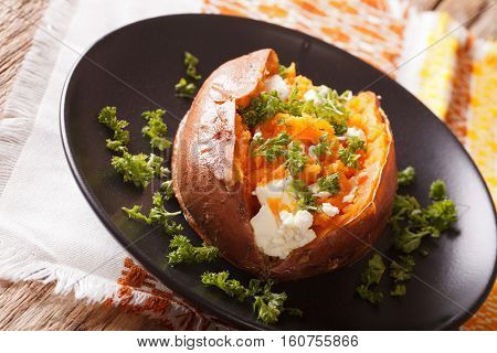 Sweet Potatoes Baked With Cream Cheese, Butter And Parsley Close-up On A Black Plate. Horizontal