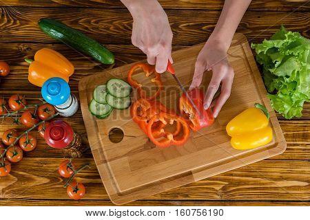 Woman in kitchen at home preparing fresh salad