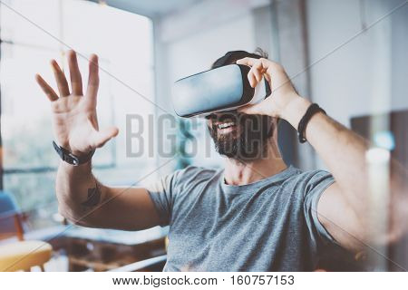Young bearded man wearing virtual reality glasses in modern interior design coworking studio. Smartphone using with VR goggles headset. Horizontal, flares effect, blurred background