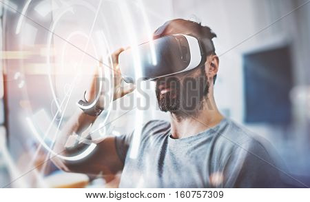 Bearded man wearing virtual reality glasses in modern interior design coworking studio. Smartphone using with VR headset. Horizontal, flares effect, blurred background