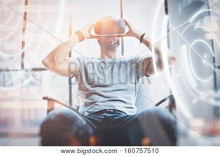 Concept of digital screen, connection and interfaces.Young beraded hipster enjoyingvirtual reality glasses in modern design loft studio.Smartphone use with VR goggles headset.Front view, blurred