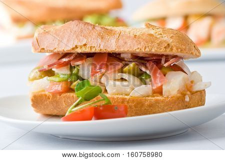 A gourmet baguette sandwich with serrano ham vegetables and cod