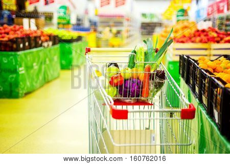 Cart with fresh fruits and vegetables in food store. Market and shopping process. Healthy eating concept. Closeup.