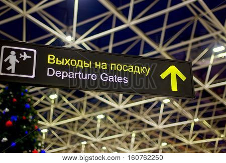 Departure sign in airport with christmas tree at background. Travel and lifestyle concept. Holidays and vacation. No people. Russian and English languages.