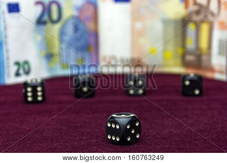 On the red velvet clearly visible black cube. In the background without the focus of four cubes and banknotes visible.