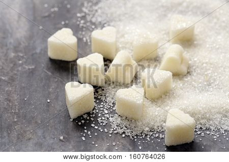Granulated sugar and refined in the shape of heart on a wooden background