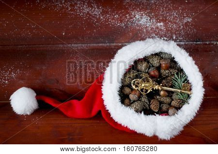 Santa Claus hat filled with pine cones and acorns flat laying on wooden boards. Golden key toy in hat