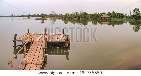 Panorama landscape with wooden pier on the Troav Kot Lake, Cambodia. Sunset in pastel colors.