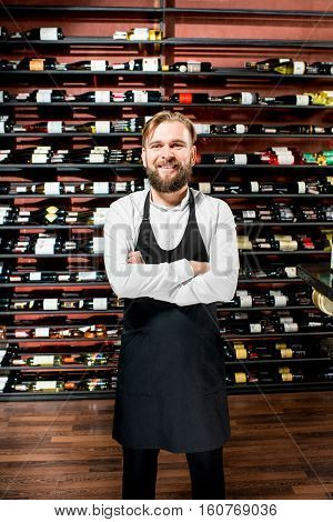 Portrait of a handsome sommelier in apron standing in front of the shelves with wine bottles at the luxury supermarket or restaurant