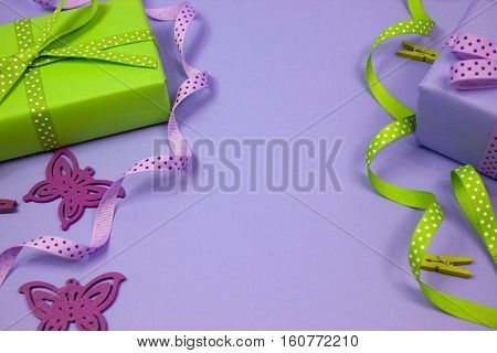 Green and lilac gift with polka dot ribbons and butterfly on lilac background