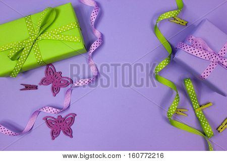 Green and lilac gift with polka dot ribbons and ornaments on lilac background