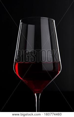 Glass of red wine with reflection on black background