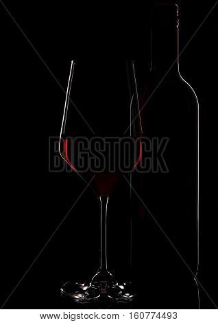 Glass of red wine with bottle close up on black background