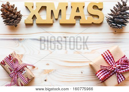 Christmas frame decorated with word xmaspine cones and gifts on wooden background with copyspace top view flat lay.