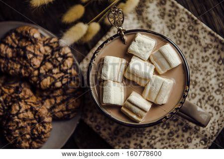 Cup of hot cocoa with marshmallow on cutting board, wooden table background