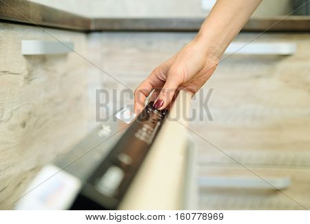 Run the dishwashing machine. Woman's finger pressing the Start button.