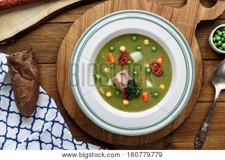 Hearty traditional Dutch pea soup with smoked sausage, rye bread and bacon. Or: 'erwtensoep met rookworst, roggebrood en spek'