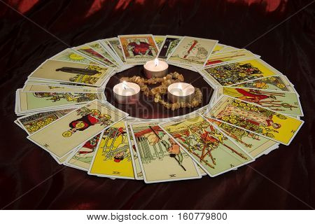 Moscow, Russia - December 4, 2016: Rider-Waite tarot cards and burning candle in center. Esoteric background.