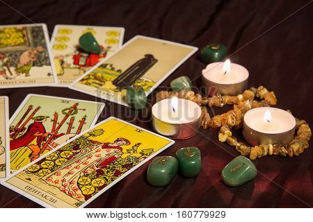 Moscow, Russia - December 4, 2016: Rider-Waite tarot cards with runes and burning candle. Esoteric background.