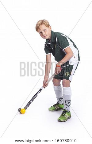 young blond teenager with field hockey stick and ball against white background