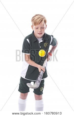 young blond boy and field hockey stick in studio