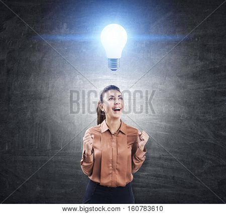 Portrait of an ecstatic woman in a brown blouse standing near a chalkboard with a glowing light bulb sketch