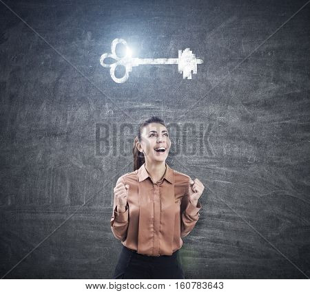 Ecstatic woman in brown is standing with an open mouth and her hands in the air near a blackboard with a glowing key sketch