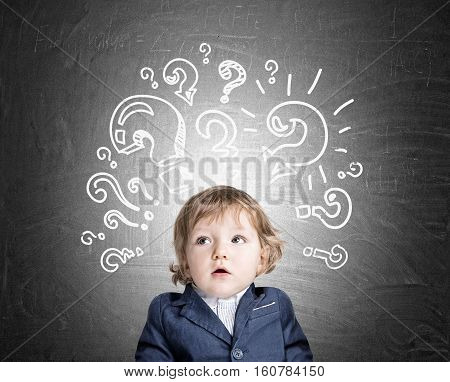 Baby Boy And Question Marks On Chalkboard