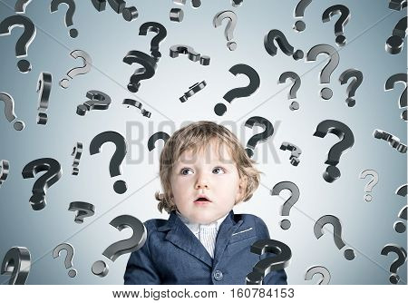 Baby Boy And Question Marks On Gray Wall