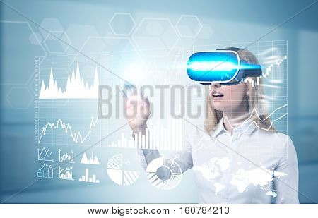 Portrait of businesswoman in virtual reality glasses working with holographic graphs. Toned image. Double exposure.