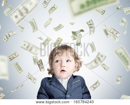 Portrait of an adorable little kid standing in his blue suit near a gray wall with dollar bills falling from the sky
