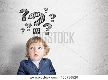 Little baby with an open mouth is wearing a blue suit and standing near a concrete wall with many question marks. Mock up