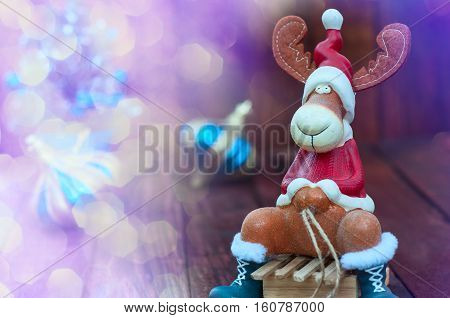 Christmas background with a toy moose on wooden sled the empty space left