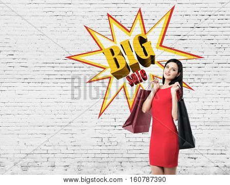 Portrait of a woman wearing red dress and holding shopping bag while standing near a brick wall with a big sale sketch on it. Mock up