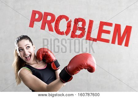 Portrait of a rookie boxer woman wearing a pair of red boxing gloves and smashing a problem word against a concrete wall.