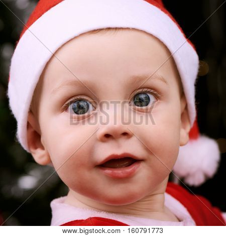 Square image of a baby boys face close up looking straight into the camera with a happy expression on his face.