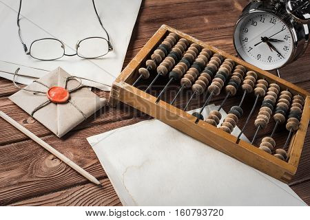 Vintage abacus envelopes and alarm clock on wooden table
